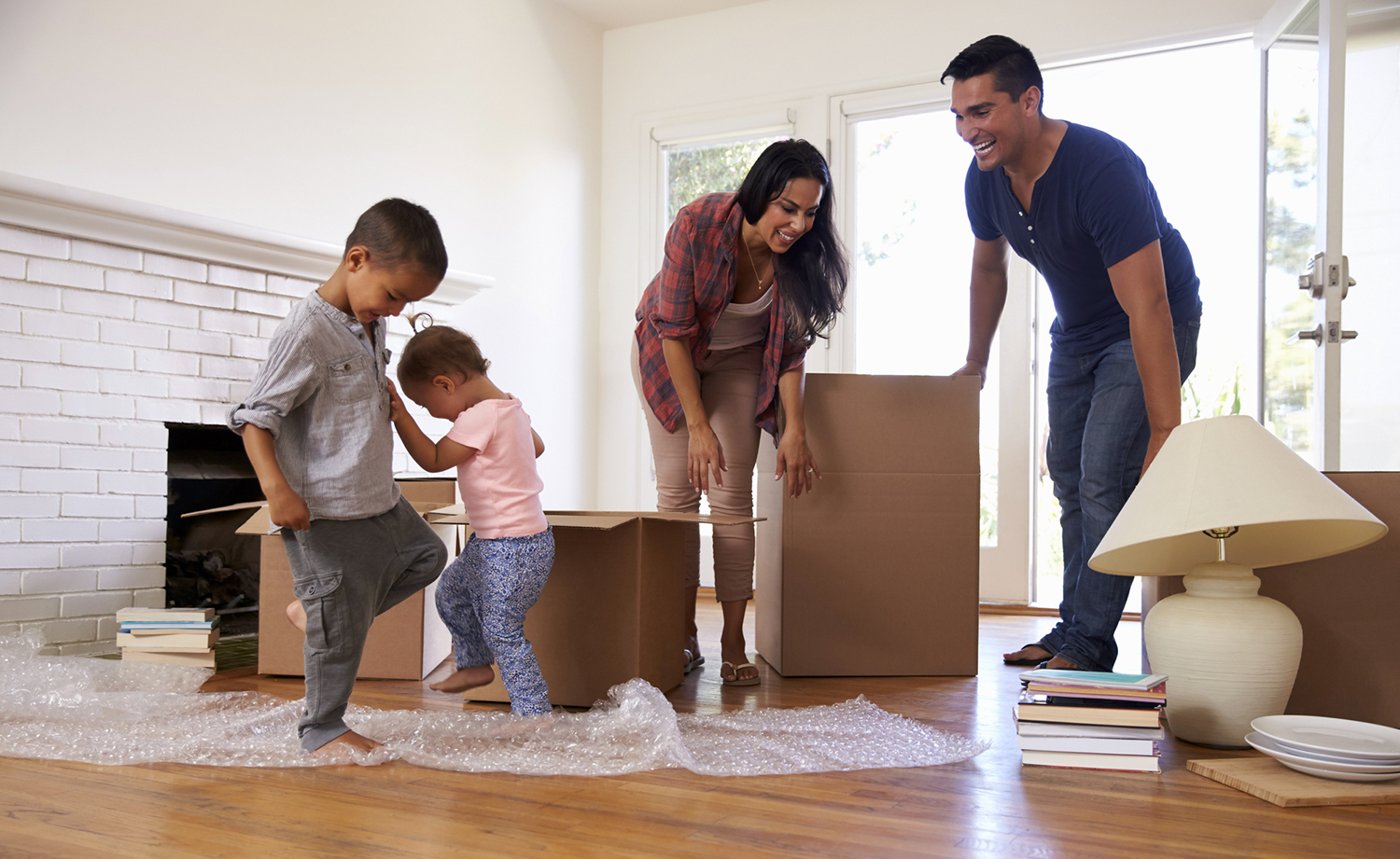 Family of four surrounded by moving boxes in their new house after thorough home inspection services were preformed