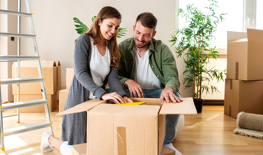 Happy couple unpacking boxes in their new house after passing a thorough home inspection