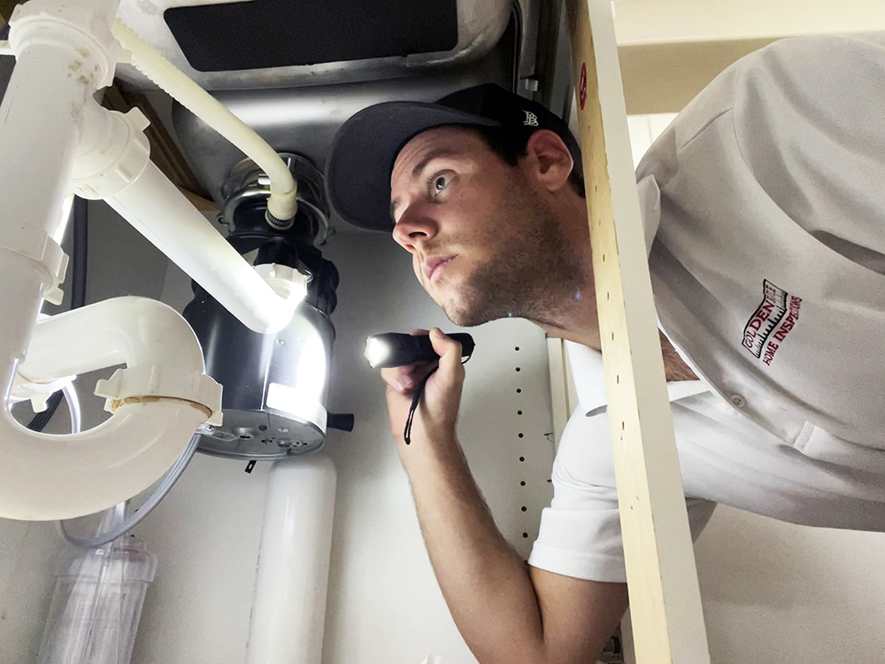 Sean Taylor, one of our certified home inspectors, inspecting under a kitchen sink